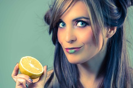 mystique: Headshot brunette with dark mystique look and green lipstick holding up an orange, grey background.