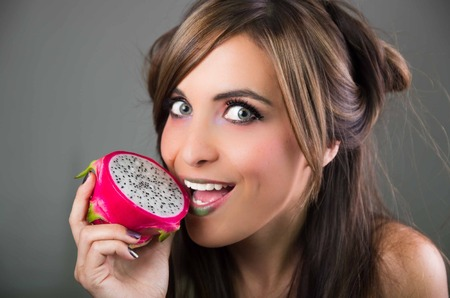 green lipstick: Headshot brunette, dark mystique look and green lipstick, holding open pink pitaya fruit next to mouth while sticking out tongue.