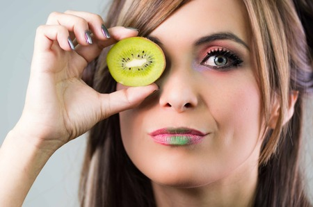 mystique: Headshot brunette, dark mystique look and green lipstick, covering one eye with open kiwi, looking into camera,