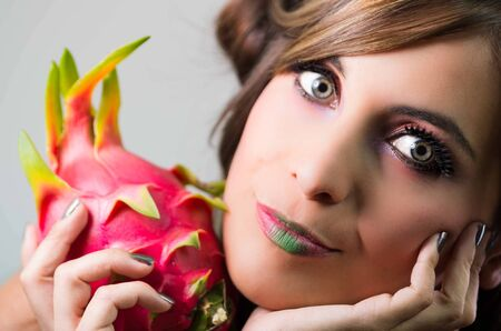 green lipstick: Headshot brunette, dark mystique look and green lipstick, holding up pink pitaya fruit, looking into camera.