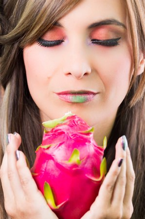 facing on camera: Headshot brunette, dark mystique look and green lipstick, holding up pink pitaya fruit with both hands facing camera.