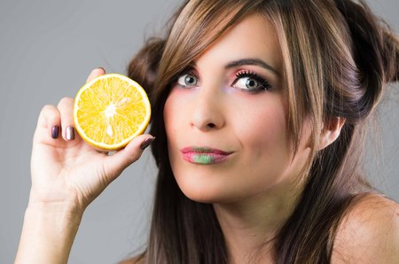 green lipstick: Headshot brunette with dark mystique look and green lipstick, holding up an orange next to face looking into camera, grey background . Stock Photo