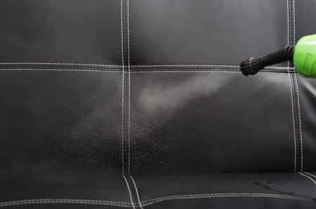 Closeup steam exiting nozzle of vapor cleaning machine, rinsing black leather couch.