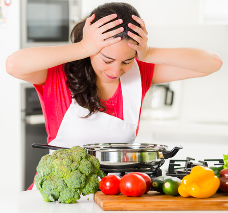 sad lady: Young woman chef holding hair in frustration, discouraged facial expression, table with kettle and vegetables. Stock Photo