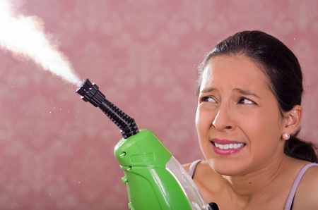 drycleaning: Brunette woman holding steam cleaner machine and vapor coming out, smiling to camera, pink background.