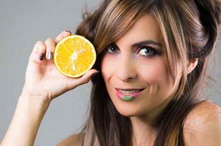 mystique: Headshot brunette with dark mystique look and green lipstick, holding up an orange next to face looking into camera, grey background . Stock Photo