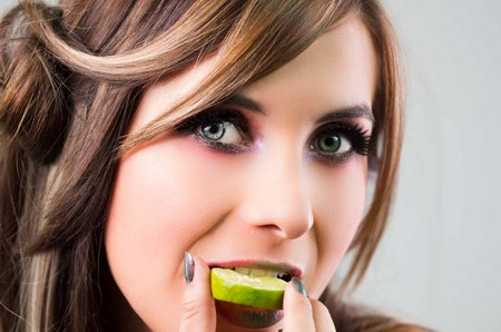 green lipstick: Headshot brunette, dark mystique look and green lipstick, biting on slice of lime while looking into camera. Stock Photo