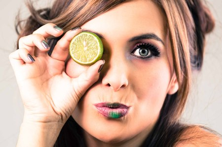 green lipstick: Headshot brunette, dark mystique look and green lipstick, covering one eye with open lime, looking into camera.