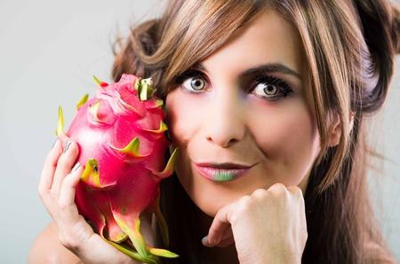 green lipstick: Headshot brunette, dark mystique look and green lipstick, holding up pink pitaya fruit, looking into camera.