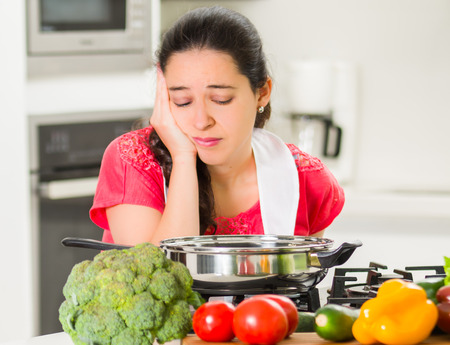 Young woman chef cooking with skeptical facial expressions, interacting frustrated body language. Stock Photo