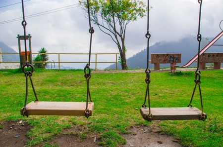 yelllow: Yelllow colored playground swing located in Andes mountains Ecuador, spectacular green background and blue sky.