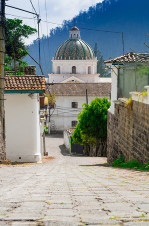 colonial building: Charming village located outside Quito Ecuador with bridgestone road leading down to dome tower of spanish colonial building.