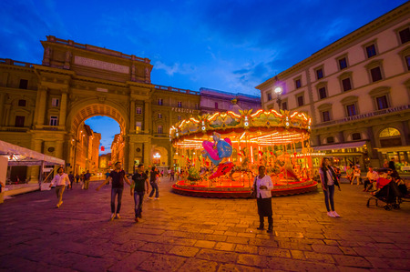 iluminated: FLORENCE, ITALY - JUNE 12, 2015: Carousel at night iluminated in the middle of the square in Florence. Different forms waitting for childrens, people walking around.