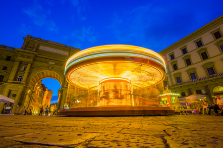 iluminated: FLORENCE, ITALY - JUNE 12, 2015: Carousel at night iluminated in the middle of the square in Florence. Unidentified tourists waitting around.
