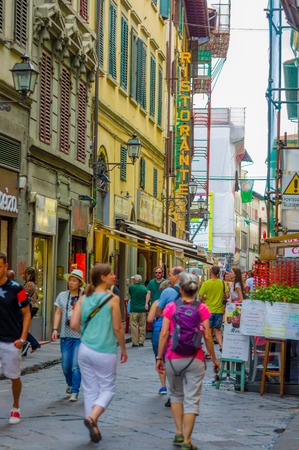 comercial: FLORENCE, ITALY - JUNE 12, 2015: Tourists and people crossing into a comercial street, a lots of shops on the sides. A new contruction on the right. Pinturesque street.