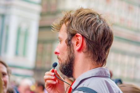 guia turistico: FLORENCIA, ITALIA - 12 DE JUNIO, 2015: guía italiana de cerca, micrófono hablando en nombre de un grupo, verano