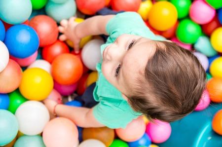 niños riendose: bebé adorable que lleva turquesa camiseta de juego de bolas de plástico de colores disparó desde ángulo por encima. Foto de archivo