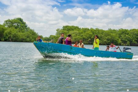 fishingboat: Muisne, Ecuador - March 16, 2016: Group of people, adults and kids inside typical blue fishingboat driving alongside shore, green trees background. Editorial