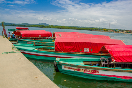 fishingboats: Muisne, Ecuador - March 16, 2016: Several typical fishingboats parked at local pier with pacific ocean background.