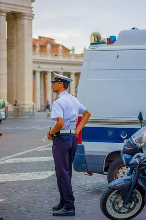 motor officer: VATICAN, ITALY - JUNE 13, 2015: Elegant italian police preparing himself, next to a car and moto. Blue uniform on the street Editorial