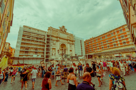 fontana: ROME, ITALY - JUNE 13, 2015: La Fontana di Trevi is the biggest fountaine with fourty metters frontal size, reconstruction period with visitors around. Editorial