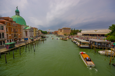 water transportation: VENICE, ITALY - JUNE 18, 2015: Big boats sailing on Venice canals, turists waitting for water transportation. Spectacular view. Editorial