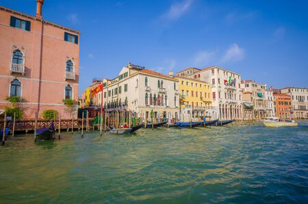 water transportation: VENICE, ITALY - JUNE 18, 2015: Nice and pinturesque buildings in Venice, Italy flags on hotels. Little port to take water transportation.
