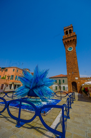 Murano: MURANO, ITALY - JUNE 16, 2015: Blue star sculpture made by glass on the center of Murano. Handmade work with a brick tower on the back.