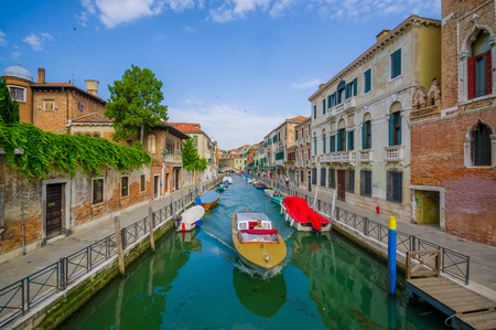 water transportation: VENICE, ITALY - JUNE 18, 2015: Venice canal with various boats on the sides and unidentified men sailing a boat in the middle. Water transportation