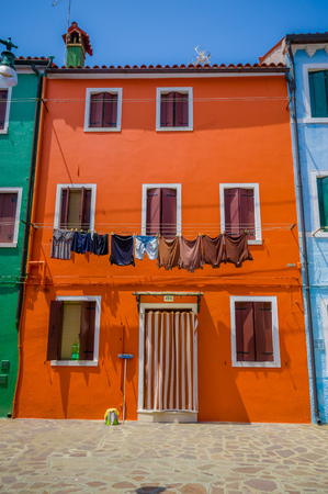 wet clothes: BURANO, ITALY - JUNE 14, 2015: Little house in orange color, various windows and wet clothes outside. Editorial