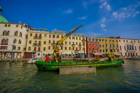 green boat: VENICE, ITALY - JUNE 18, 2015: Green boat with a crane parking in Venice canals, equipment to help. Editorial