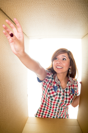 arm extended: White background with cardboard box on the middle, girl trying to get something from the corner. Arm extended, dark nails