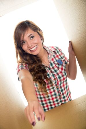 arm extended: Girl with a big smiling, one arm extended inside a box and the other holding the border. Stock Photo