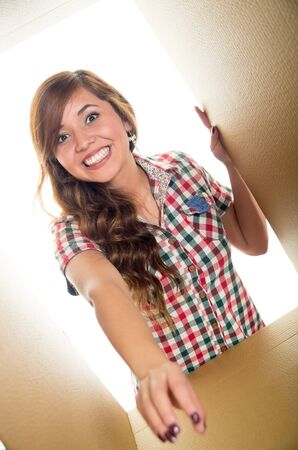 arm extended: Smiling and wavy hair girl inside a cardboard box, one arm extended and other holding the border.