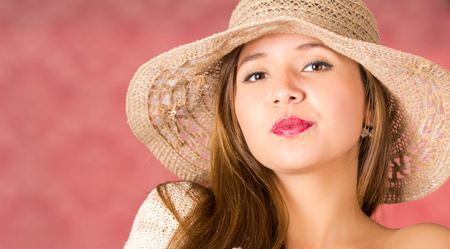 beige lips: Serious woman with a beautiful knit hat on beige color posing on a pink background. Red lips Stock Photo