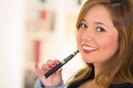 electronical: Young beautiful woman trying to smoke an electronical black cigarette, red lips and nails Stock Photo