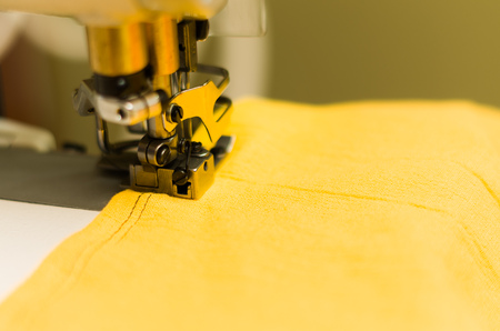 Close up of sewing machine, yellow fabric with black thread.