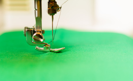 stitchwork: Close up of needle in a sewing machine, thread on this. Green fabric.