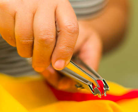 pezones: Hands manipulating special nipplers to make a zipper, red color