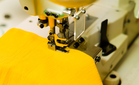 stitchwork: Sewing machine ready to start with yellow fabric, steel equipment.