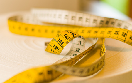 centimeters: Yellow tape measure rolled at the top of a table, centimeters and meters measurement, close up