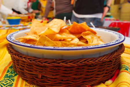 american table: Bowl of crunchy delicous tortilla chips sitting on native american table cloth.