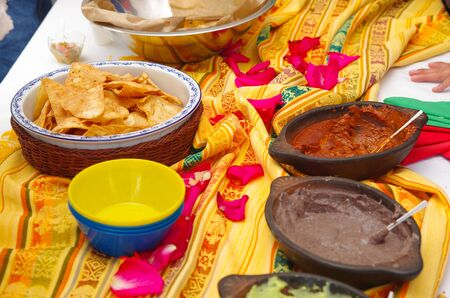 american table: Bowl of crunchy delicous tortilla chips sitting on native american table cloth, next to different salsas. Stock Photo