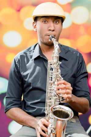 african sax: African man wearing sixpence hat and dark shirt playing saxophone, facing camera.