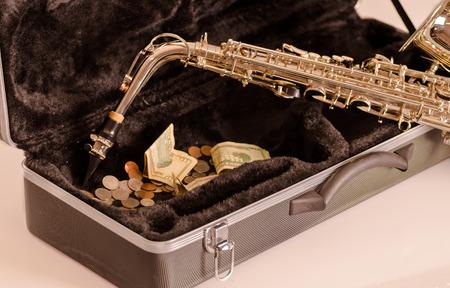instrumental: Shiny saxophone lying across open instrumental casing with black velvet interior and pile of money inside .