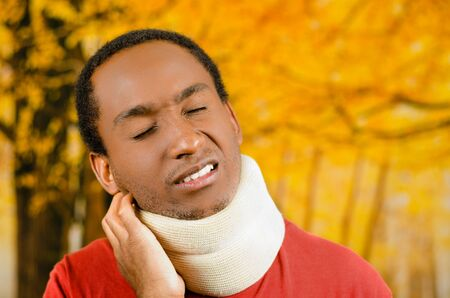 neck brace: Injured black hispanic male wearing neck brace, holding hands in pain around support making faces of agony, yellow abstract background.
