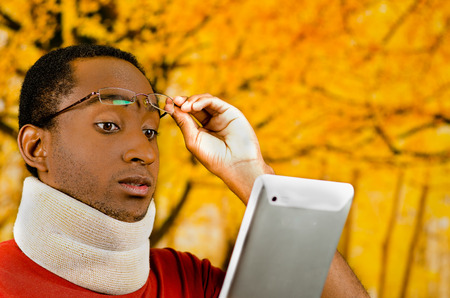 neck brace: Injured young positive black hispanic male wearing neck brace, holding tablet and reading from screen lifting glasses up forehead, yellow abstract background.