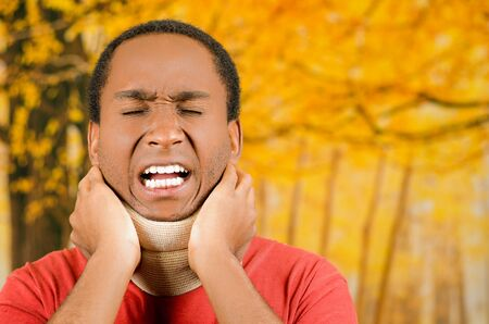 neck brace: Injured young positive black hispanic male wearing neck brace, holding hands in pain around support making faces of agony, yellow abstract background.