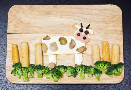 ham and cheese: Cow with landscape made from cheese, white carrots, broccoli, mushroom and ham, artistic food concept.