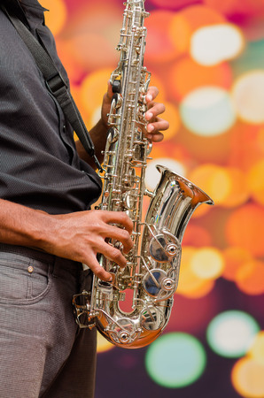 african sax: Man wearing dark shirt and jeans playing saxophone, posing from profile angle. Stock Photo